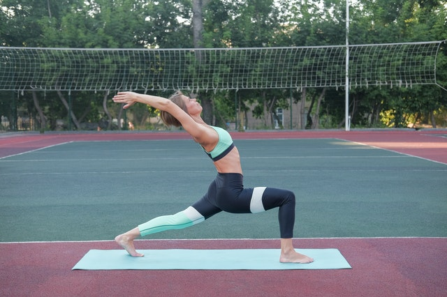 Woman standing in Crescent Lunge pose on yoga mat